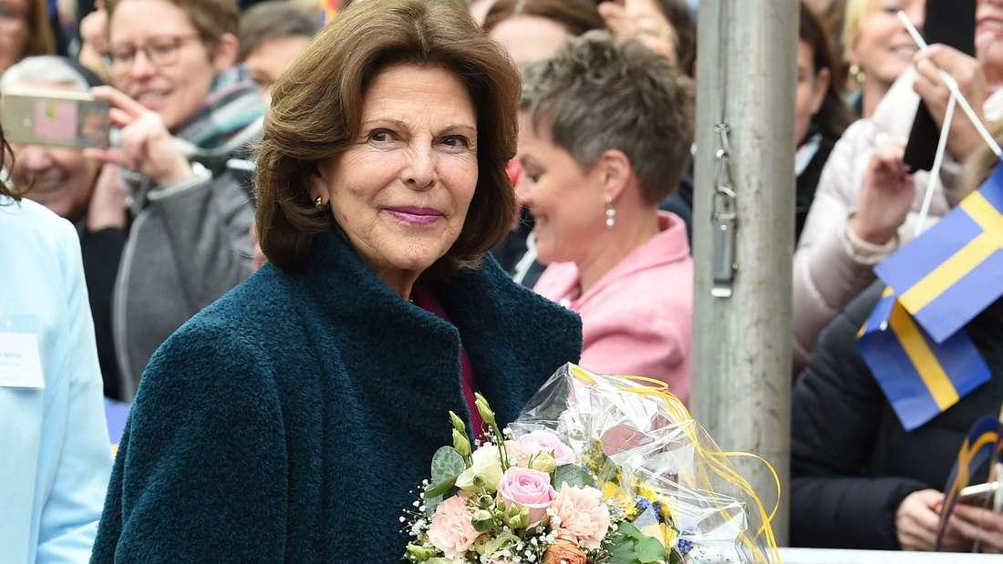 Königin Silvia von Schweden hält einem Blumenstrauß in der Hand.