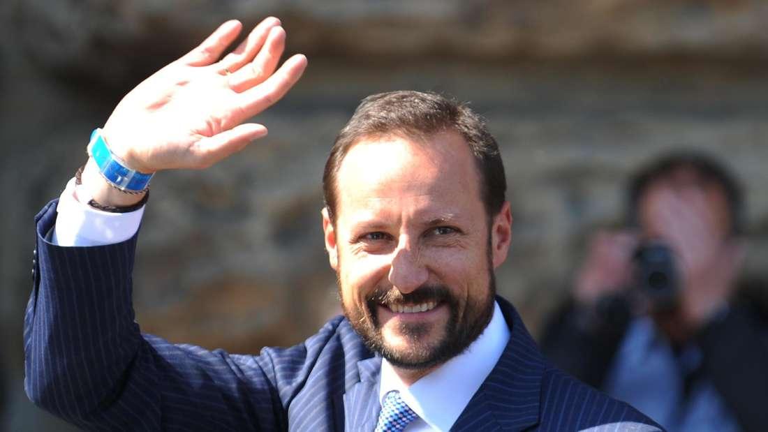 Kronprinz Haakon von Norwegen trägt einen dunkelblauen Anzug und winkt lächelnd in Richtung Fotografen.