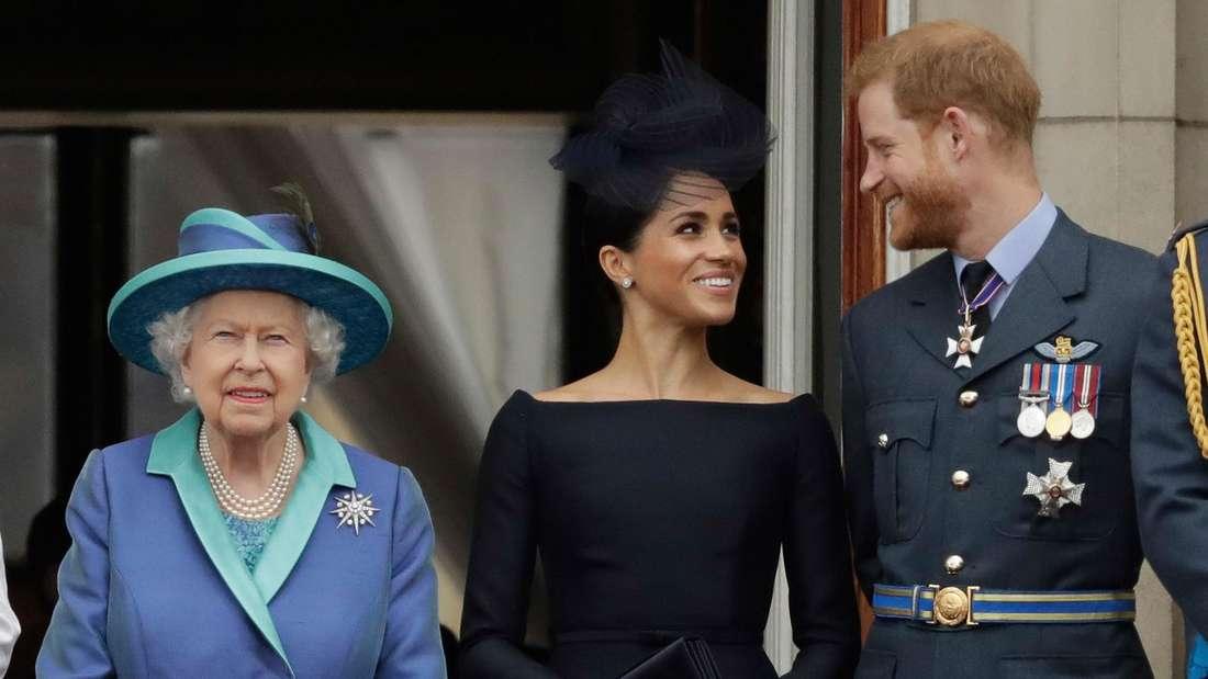 Queen Elizabeth II. steht neben Herzogin Meghan und Prinz Harry