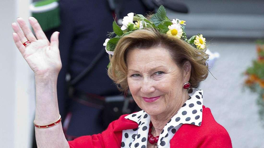 Königin Sonja von Norwegen trägt einen Blumenkranz und eine rote Jacke und winkt in Richtung Fotografen.
