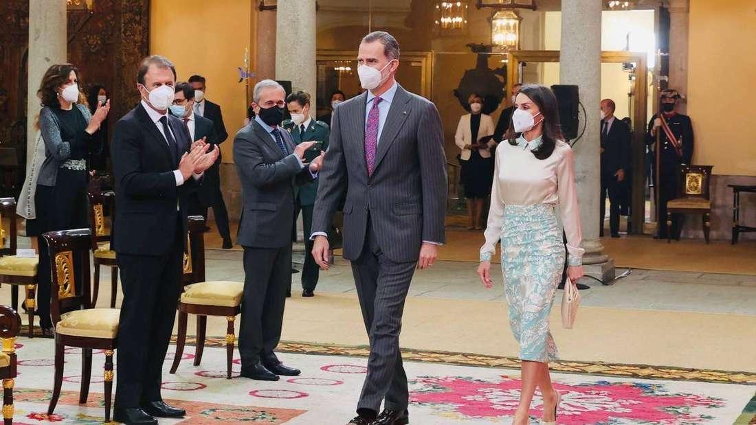 König Felipe von Spanien und Königin Letizia laufen unter Applaus nebeneinander her.