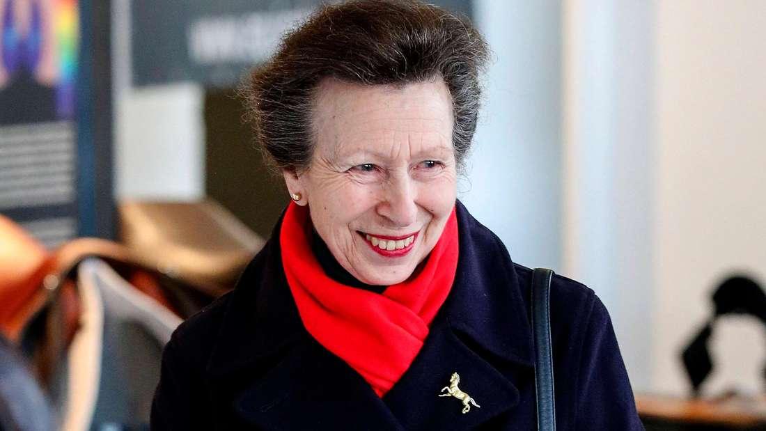 Prinzessin Anne trägt einen dunklen Mantel, einen roten Schal und eine goldene Brosche in Form eines Pferdes.