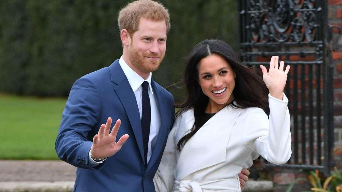 Prinz Harry und Meghan Markle stehen nebeneinander und winken