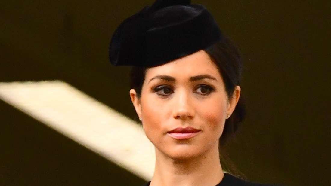 Herzogin Meghan trägt schwarze Kleidung und blickt besorgt zur Seite.