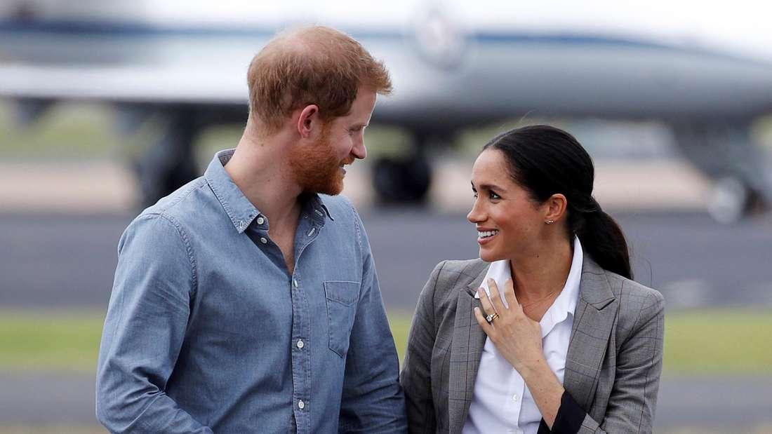Prinz Harry und Herzogin Meghan halten Händchen und schauen sich an.