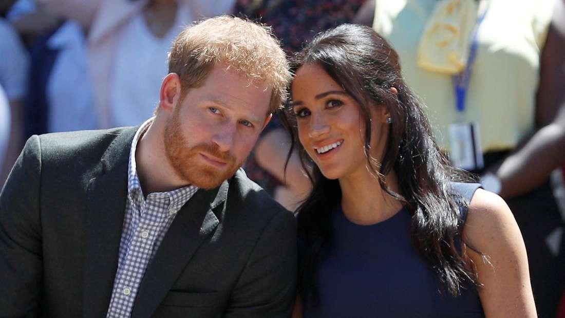 Prinz Harry sitzt neben seiner Frau Herzogin Meghan.