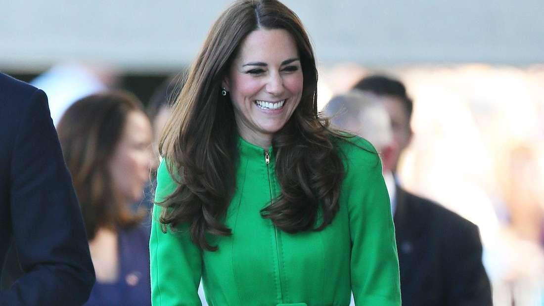 Herzogin Kate tägt ein grünes Kleid und lacht.