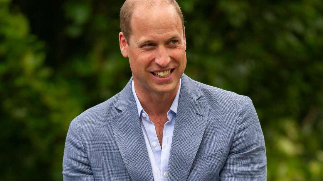 Prinz William trägt ein hellblaues Hemd und ein graublaues Sakko und schaut lächelnd zur Seite.