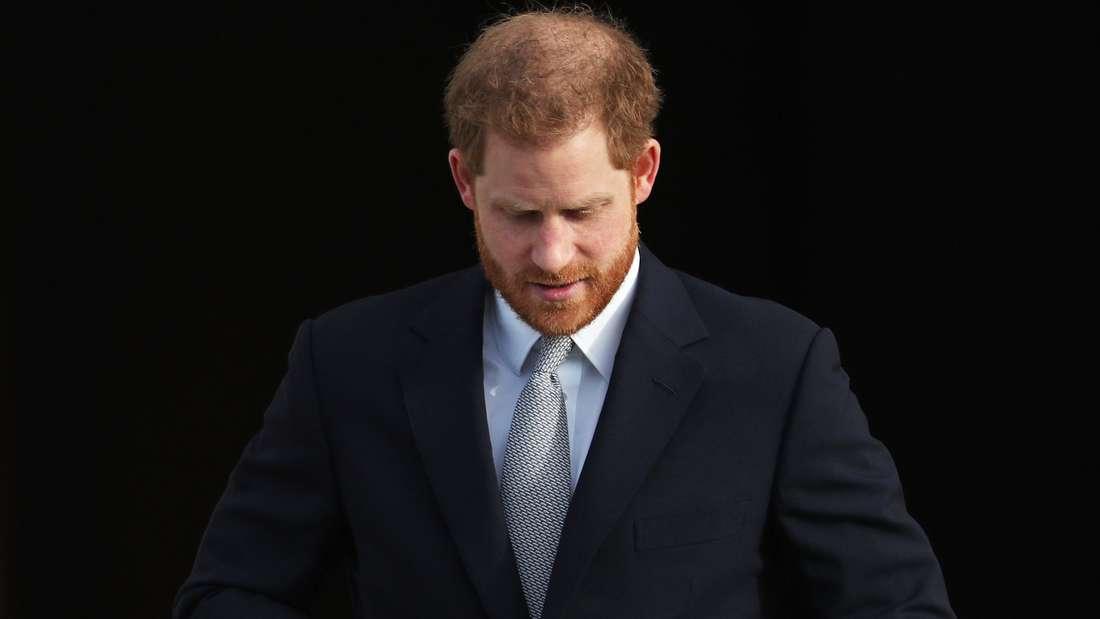 Prinz Harry schaut nach unten und knöpft sich sein Sakko zu.