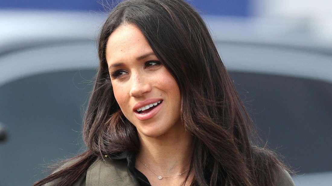 Herzogin Meghan trägt ein schwarzes Oberteil und eine dunkelgrüne Jacke und schaut zur Seite.