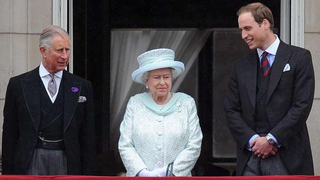 Prinz Charles steht neben Queen Elizabeth II. und Prinz William