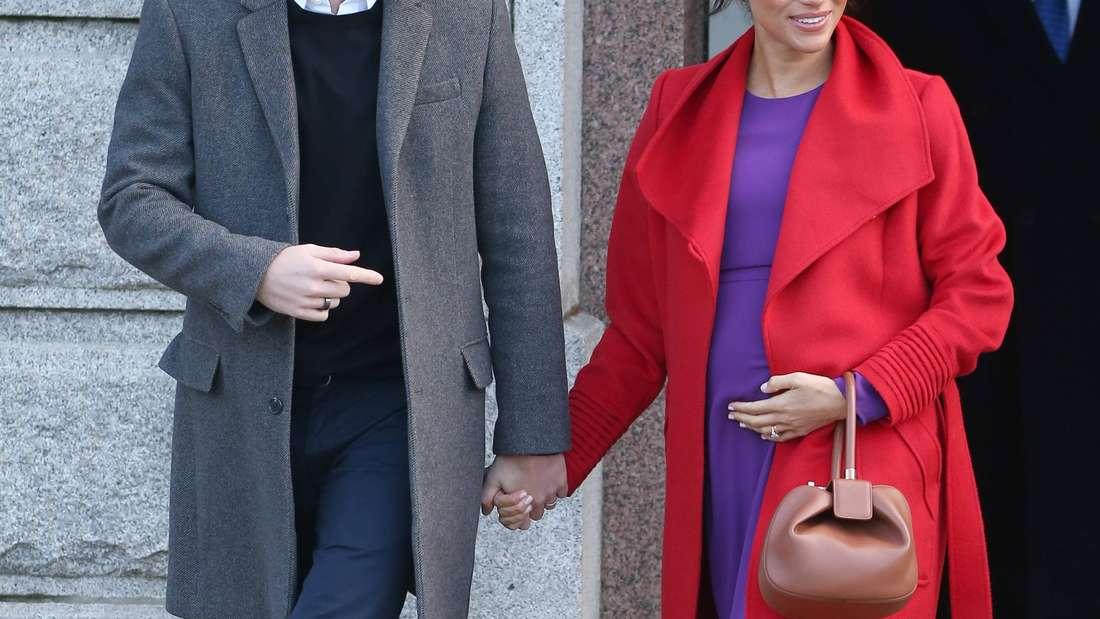 Prinz Harry und Herzogin Meghan, die schwanger ist, halten Händchen.