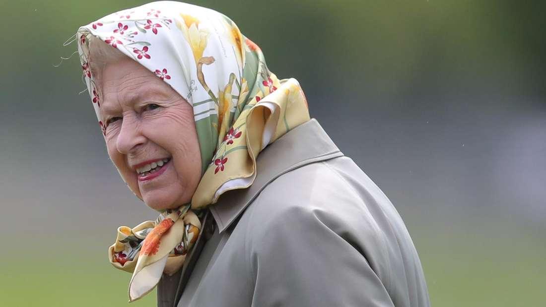 Queen Elizabeth II. trägt einen Mantel und ein Kopftuch und schaut zur Seite (Symbolbild).