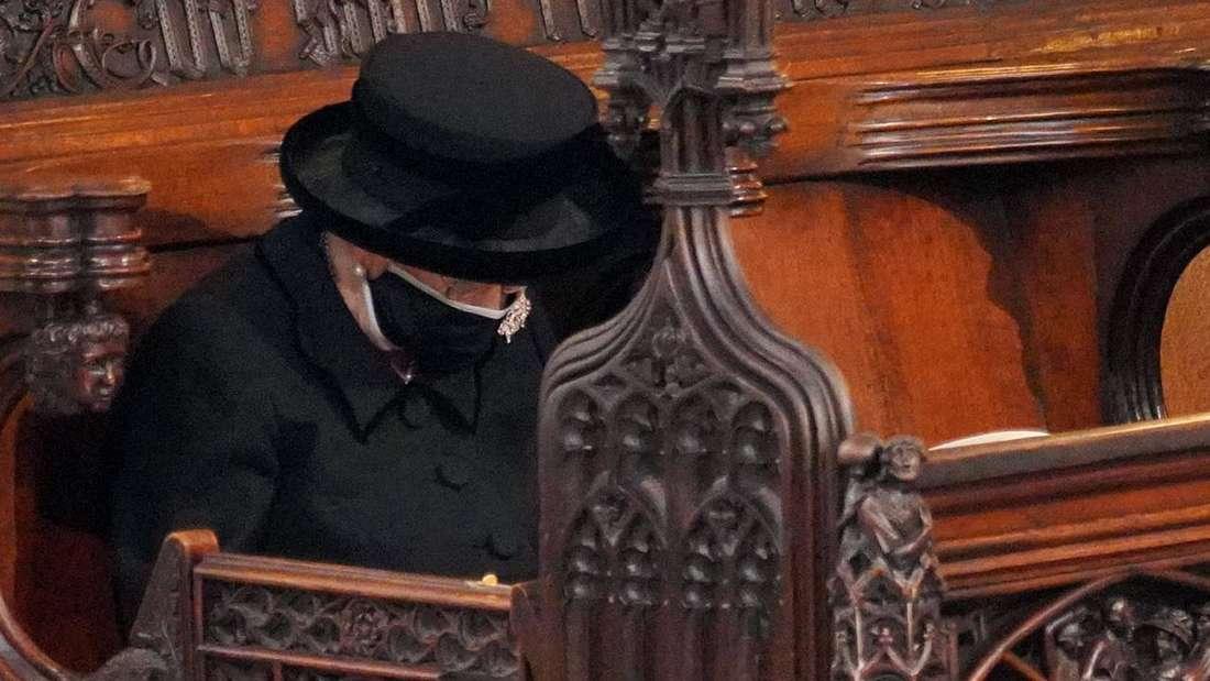 Queen Elizabeth II. sitzt mit gesenktem Kopf auf einer Bank in der  St. George's Chapel.