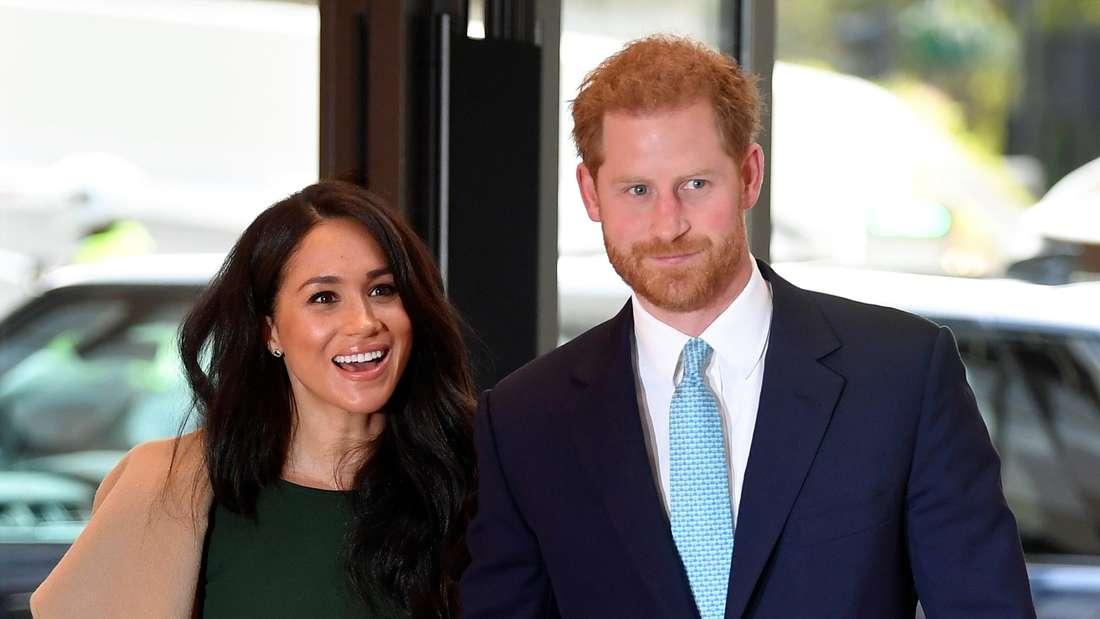 Prinz Harry und Herzogin Meghan gehen gemeinsam nebeneinander und sehen erfreut auf das, was ihnen entgegenkommt