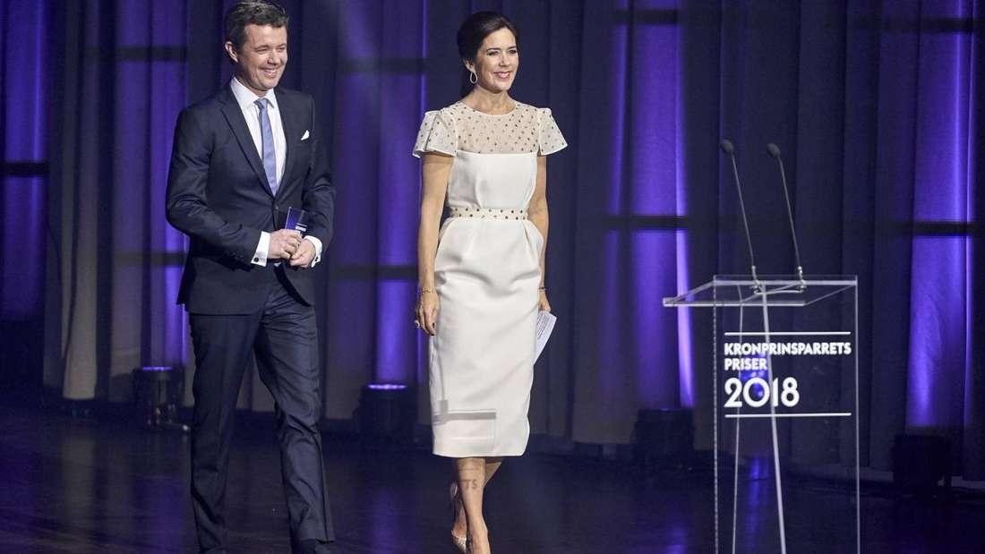 Das dänische Kronprinzenpaar läuft auf ein Rednerpult zu.