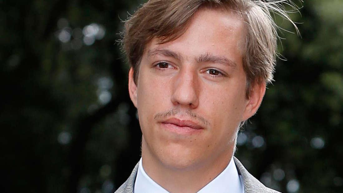 Prinz Louis von Luxemburg trägt ein graues Sakko und eine orangene Krawatte