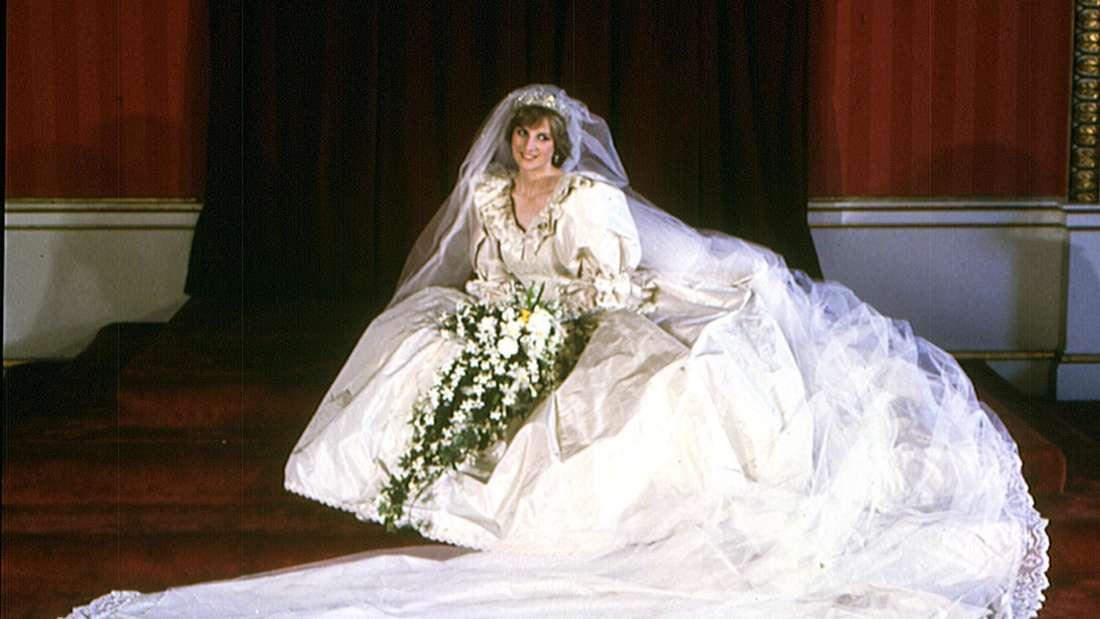 Prinzessin Diana sitzt mit drapierter Schleppe und Schleier im opulenten Hochzeitskleid Porträt für die Fotografen und lächelt schüchtern