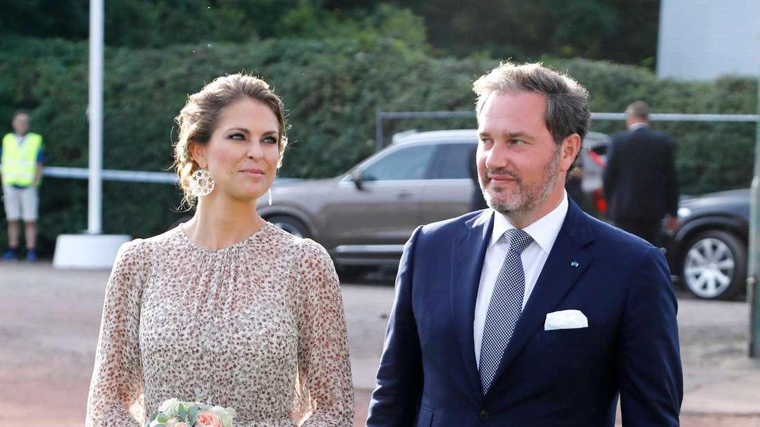Prinzessin Madeleine hat einen Blumenstrauß in der Hand und läuft neben ihrem Ehemann Chris O'Neill her.