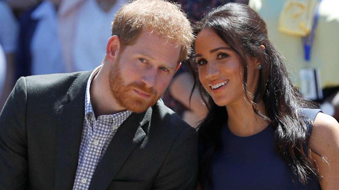 Prinz Harry und Herzogin Meghan sitzen mit dem Köpfen zueinander geneigt nebeneinander.