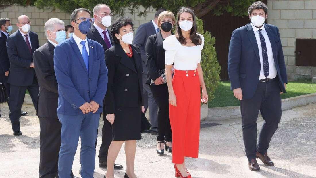 Königin Letizia trägt ein helles Top und eine rote Hose und steht neben mehreren Männern und Frauen.