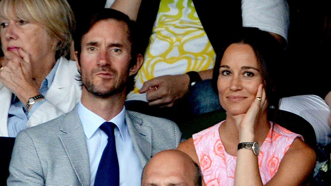 Pippa und James Matthews sitzten bei einem Tennisturnier nebeneinander. Pippa schaut direkt in die Kamera