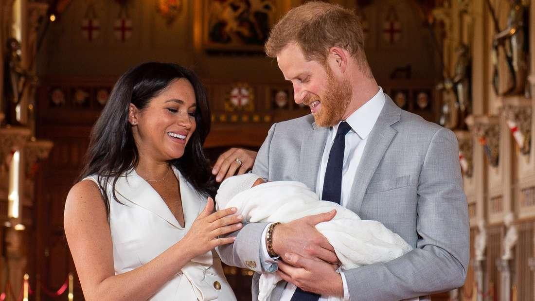 Herzogin Meghan blickt ihren Sohn Archie an, den Prinz Harry im Arm trägt.