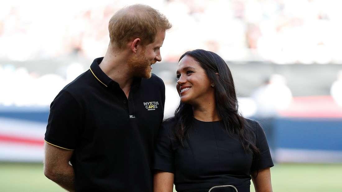 Prinz Harry und Herzogin Meghan blicken sich an und lächeln.