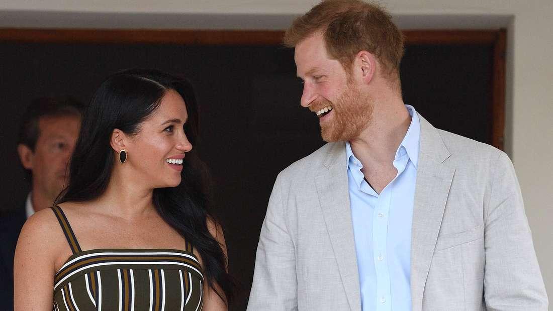 Herzogin Meghan und Prinz Harry halten Händchen und schauen sich strahlend an.