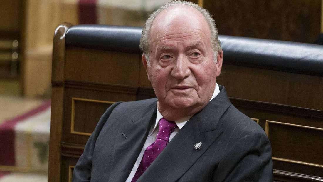 Altkönig Juan Carlos von Spanien trägt Anzug und Krawatte und blickt zur Seite.