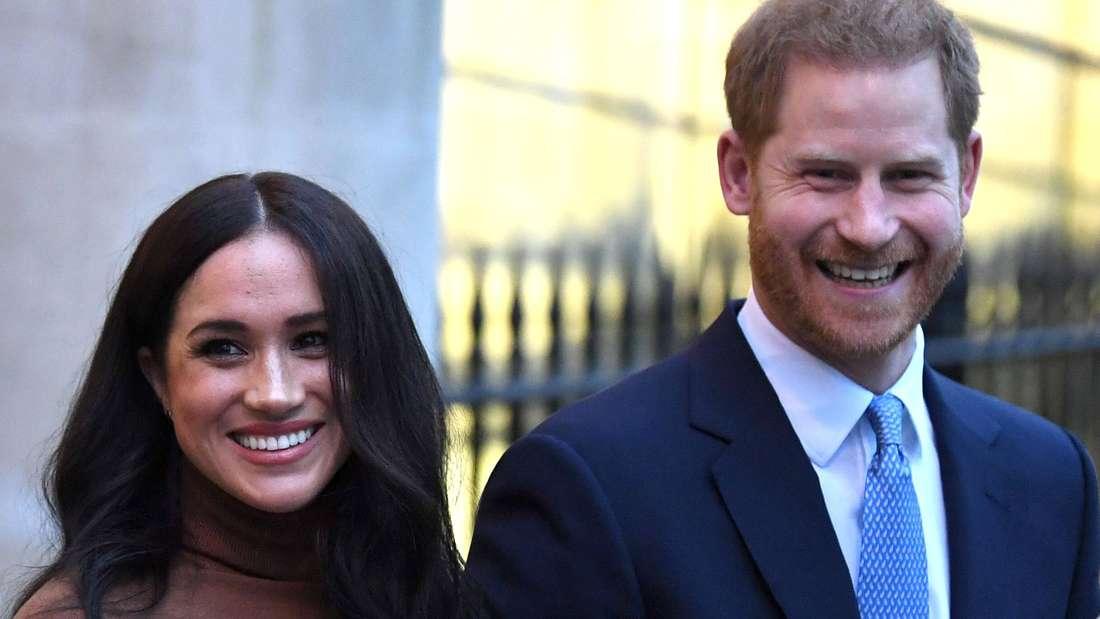 Herzogin Meghan und Prinz Harry lächeln und stehen nebeneinander.