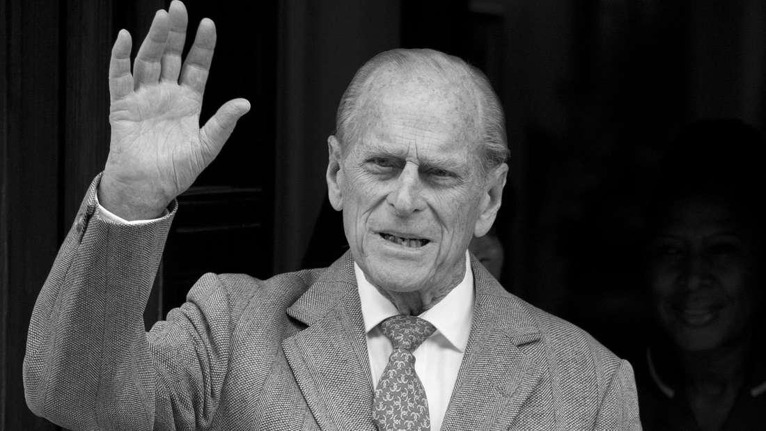 Prinz Philip trägt Sakko und Krawatte und winkt mit seiner rechten Hand.