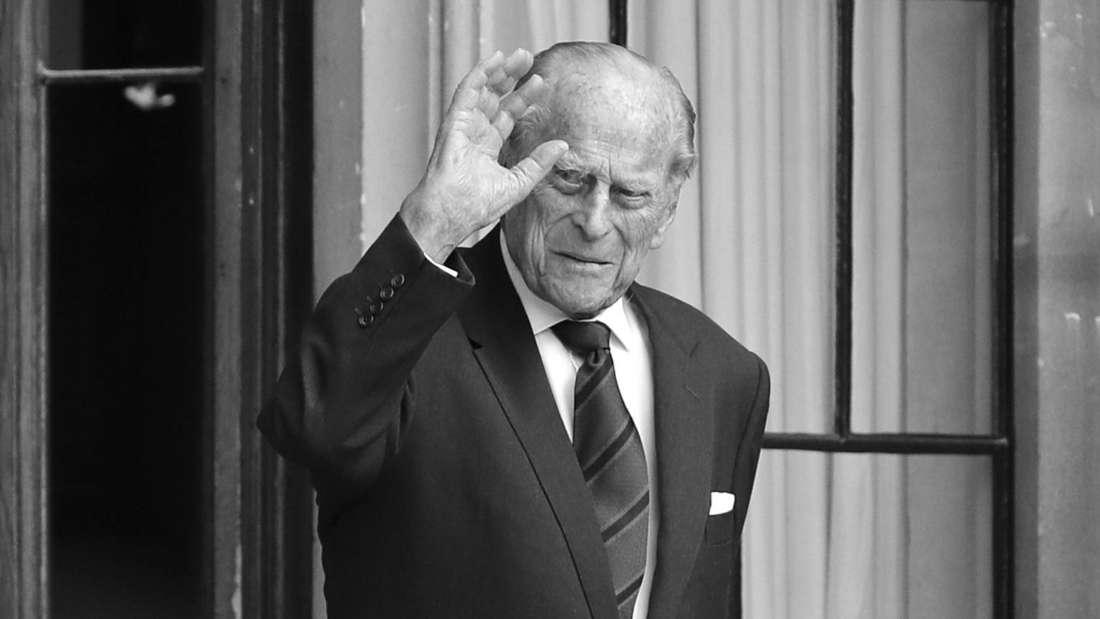 Prinz Philip trägt Sakko, Hemd und Krawatte und winkt.