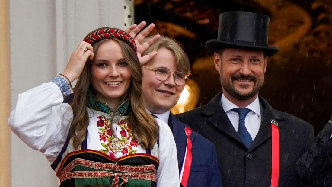 Prinzessin Ingrid Alexandra steht lächelnd vor ihrem Bruder Sverre Magnus und ihrem Vater Haakon.