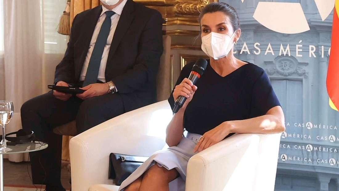 Königin Letizia sitzt in einem weißen Sessel und hält ein Mikrofon in der Hand.