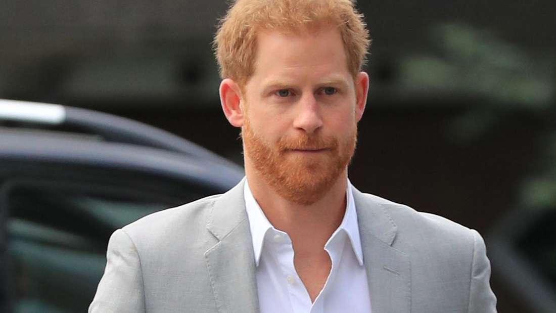 Prinz Harry geht in einem grauen Anzug vom Auto kommend zu einem Termin