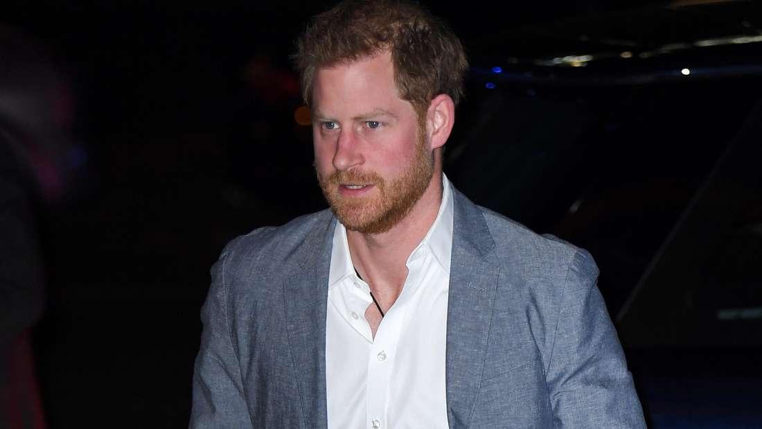 Prinz Harry trägt ein weißes Hemd und ein graues Sakko und guckt angestrengt.