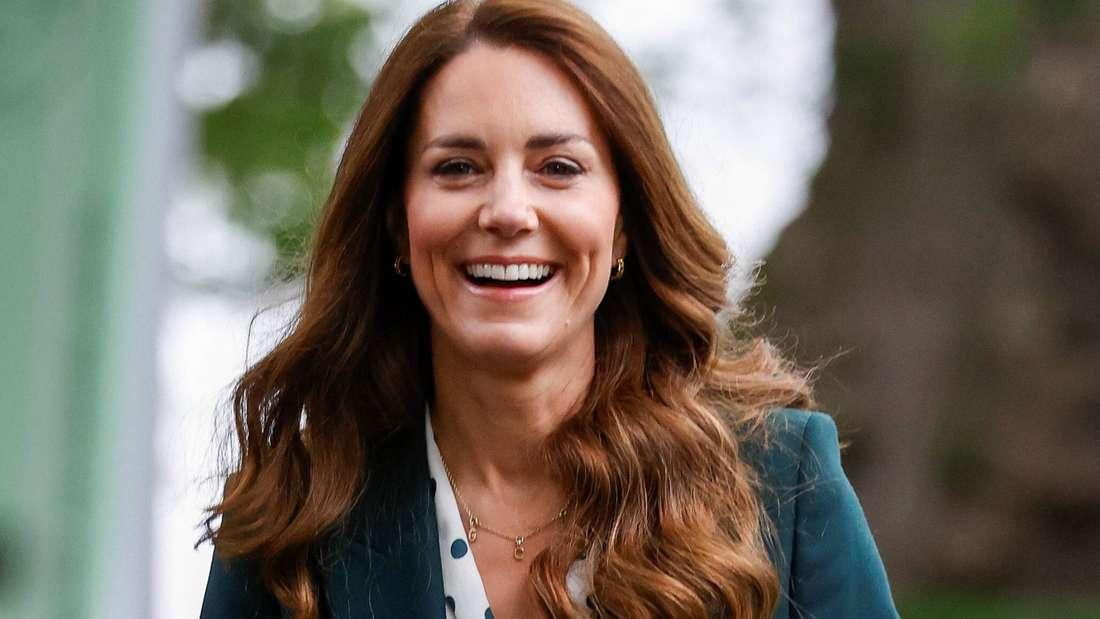 Herzogin Kate trägt eine helle Bluse und einen grünen Blazer und lacht.