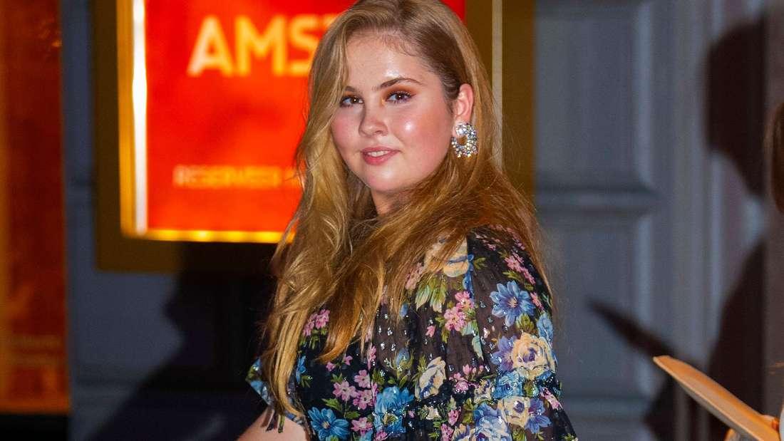Kronprinzessin Amalia der Niederlande trägt ein Abendkleid und schaut im Gehen zur Seite.