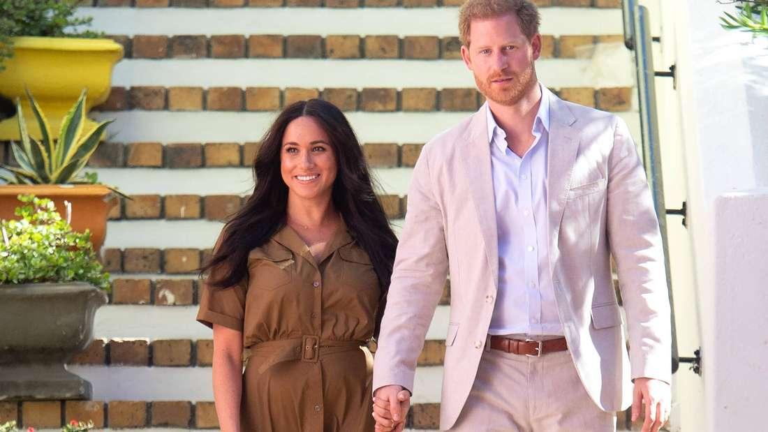 Prinz Harry und Herzogin Meghan laufen Hand in Hand eine Treppe hinunter.