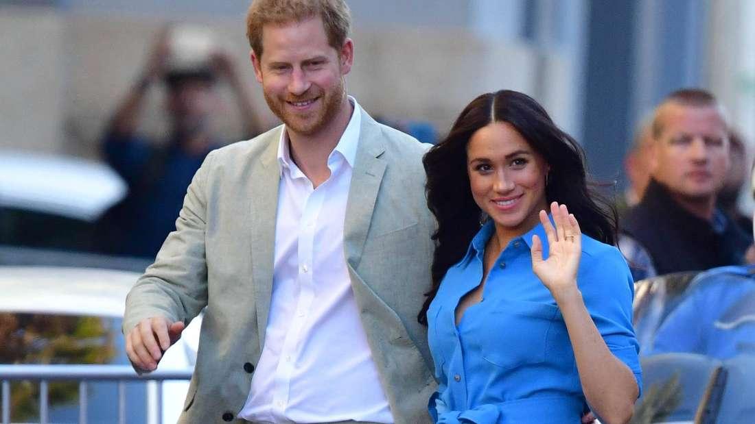 Prinz Harry und Herzogin laufen nebeneinander her, während Meghan mit der linken Hand winkt.