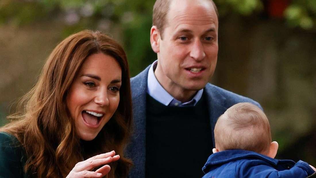 Herzogin Kate und Prinz William sprechen mit einem Baby, das von seiner Mutter gehalten wird.