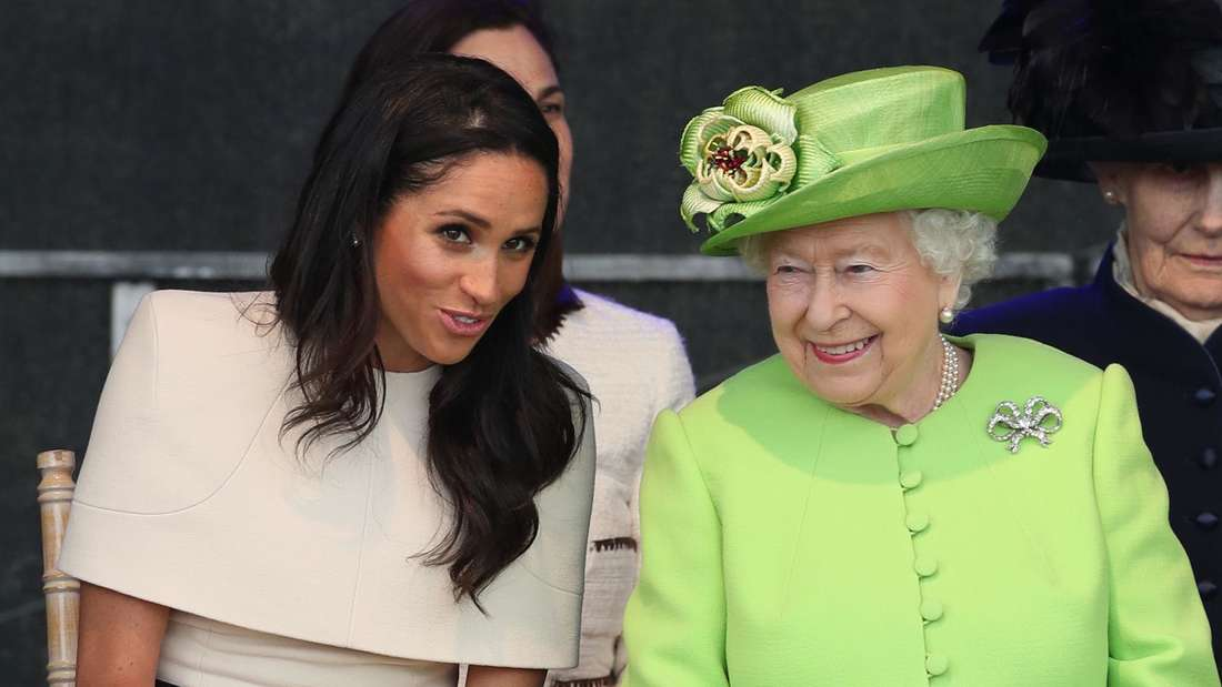 Herzogin Meghan spricht mit Queen Elizabeth II., die neben ihr sitzt.
