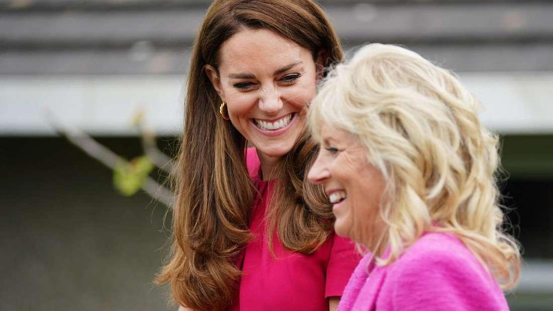 Herzogin Kate und Jill Biden stehen lachend nebeneinander.