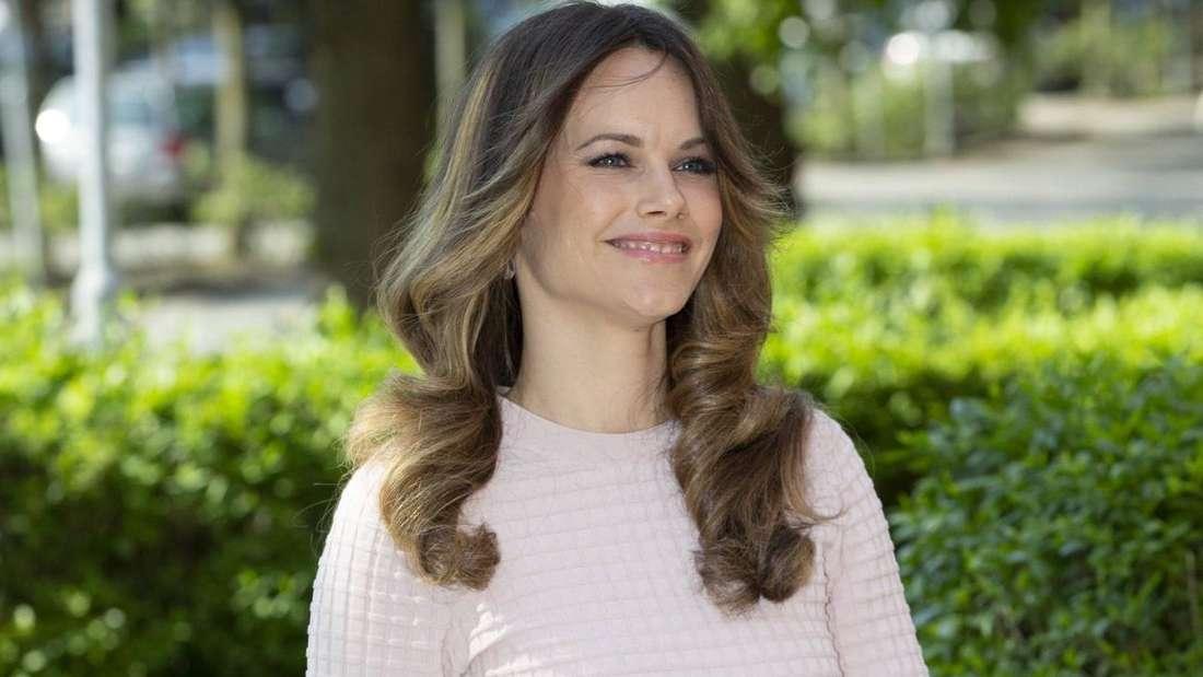 Prinzessin Sofia trägt einen hellen Pullover und läuft lächelnd vor einer Hecke entlang (Symbolbild).