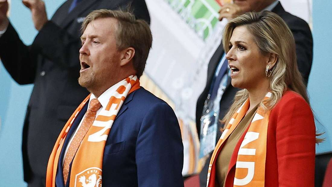König Willem-Alexander und Königin Máxima stehen im Stadium nebeneinander und singen.