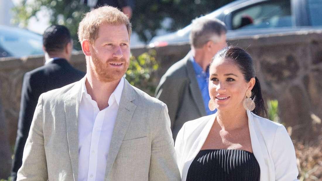 Prinz Harry und Herzogin Meghan halten Händchen und laufen nebeneinander.