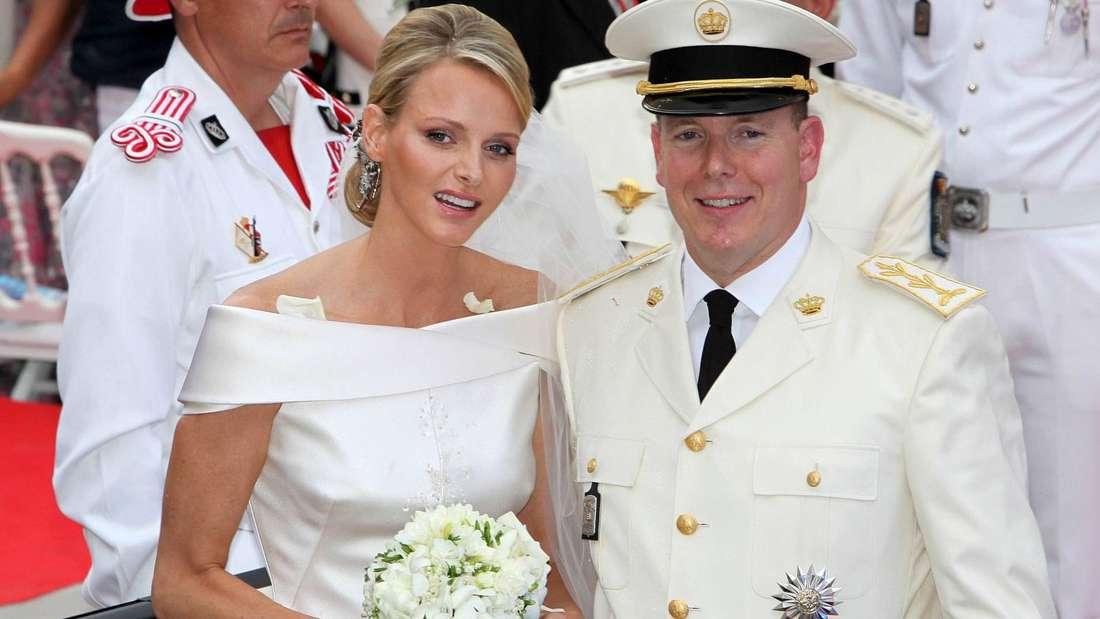 Fürstin Charlène und Fürst Albert stehen bei ihrer Hochzeit lächelnd nebeneinander.