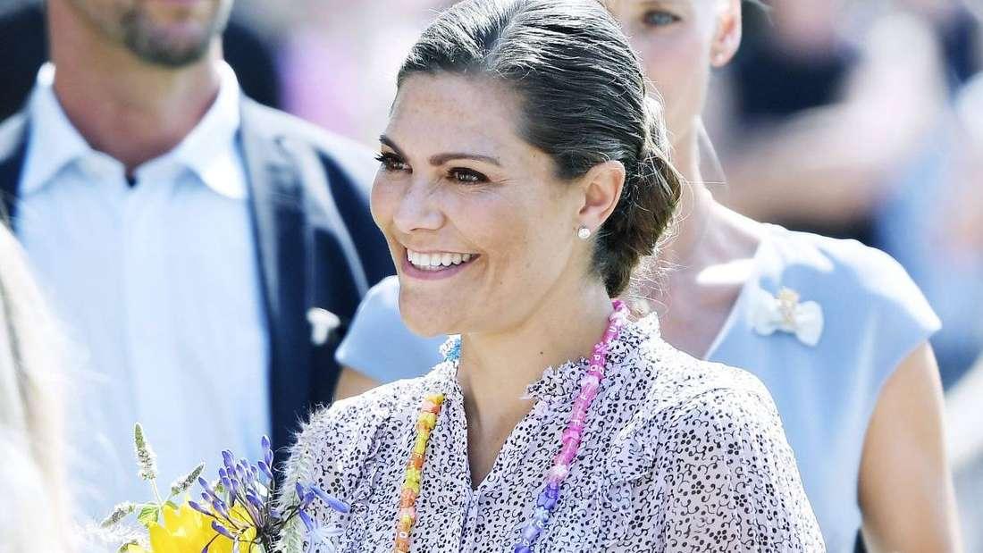Kronprinzessin Victoria von Schweden hält Blumen in der Hand und lächelt.