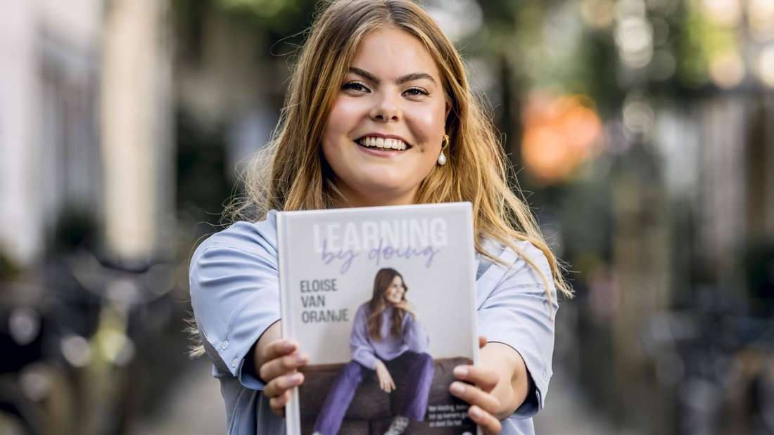 """Gräfin Eloise von Oranje-Nassau hält ihr Buch """"Learning by Doing"""" in die Kamera und grinst."""